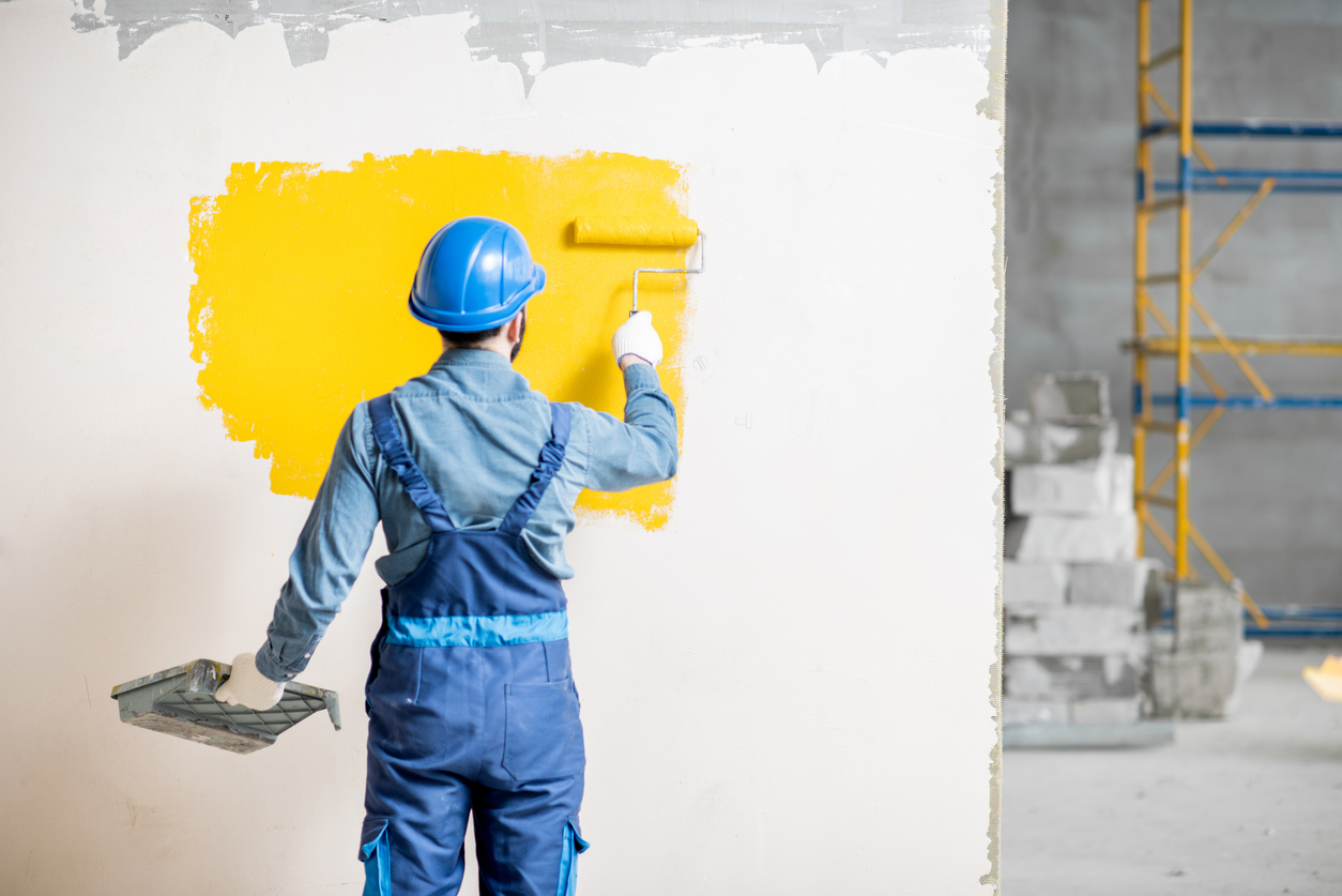Workamn painting wall indoors